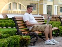 Mann, der einen Laptop auf einer allgemeinen Bank verwendet Stockfotografie