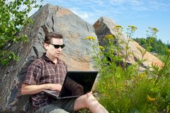 Mann, der einen Laptop im Sommertag verwendet lizenzfreies stockfoto