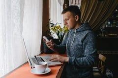 Mann, der einen Laptop und ein Mobiltelefon in einem Café verwendet Junger Mann, der c trinkt Lizenzfreie Stockbilder