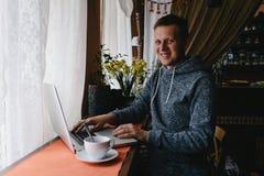 Mann, der einen Laptop und ein Mobiltelefon in einem Café verwendet Junger Mann, der c trinkt Stockbild