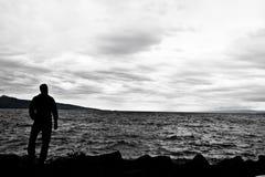 Mann, der einen rauen See aufpasst Stockfotografie
