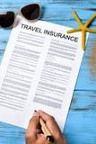 Mann, der einen Reiseversicherungsversicherungsvertrag unterzeichnet stockfotografie
