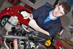 Mann, der einen Schlüssel über einem Automotor anhält Lizenzfreies Stockfoto