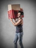 Mann, der einen schweren Kasten trägt Stockfoto