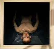 Mann, der in einen sensorischen Entzug-Isolierungs-Behälter schwimmt Stockbilder