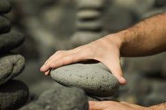 Mann, der einen Turm mit Steinen macht Stockfoto