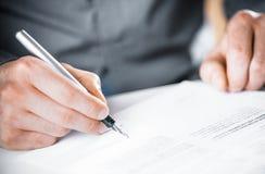 Mann, der einen Vertrag oder eine Vereinbarung unterzeichnet Stockfotos