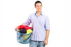 Mann, der einen Wäschekorb voll von der Kleidung hält Lizenzfreie Stockfotos