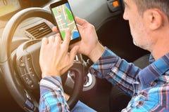 Mann, der einen Weg auf einem Smartphone in einem Auto herstellt lizenzfreie stockfotografie
