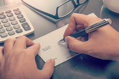 Mann, der einen Zahlungsscheck schreibt lizenzfreies stockbild
