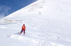Mann, der in einer geschneiten Steigung steht lizenzfreie stockbilder