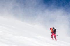 Mann, der in einer geschneiten steilen Steigung wandert lizenzfreie stockbilder