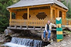 Mann, der an einer Hütte errichtet sitzt Stockfotografie