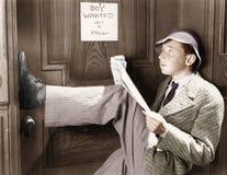 Mann, der an einer Tür mit seinen Beinen oben sich lehnt und eine Zeitung liest (alle ex Personen dargestellt sind nicht längeres Lizenzfreies Stockbild