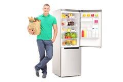 Mann, der Einkaufstüte hält und einen Kühlschrank bereitsteht stockbilder