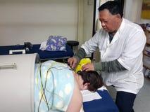 Mann, der elektrische Akupunkturtherapie von asiatischem Doktor der chinesischen traditionellen Medizin empfängt stockfotografie