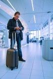 Mann, der eMail auf Flughafen überprüft stockfotografie