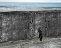 Mann, der enorme Puzzlespieltür der Betonmauer drückt Lizenzfreie Stockbilder