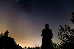 Mann, der entlang des nächtlichen Himmels mit Milchstraße anstarrt Stockbild