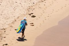 Mann, der entlang Strand mit Körper-Brettern über Schulter geht stockbild