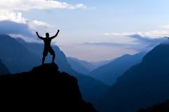 Mann, der Erfolgsschattenbild in den Bergen wandert Stockfotos