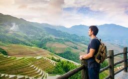 Mann, der erstaunliche asiatische Reisterrassenlandschaft genießt stockbilder