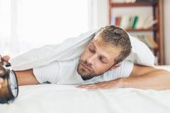 Mann, der es schwierig, morgens aufzuwachen findet lizenzfreies stockbild