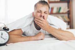 Mann, der es schwierig, morgens aufzuwachen findet lizenzfreie stockbilder