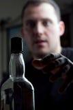 Mann, der für die Alkohol-Flasche erreicht Stockbilder