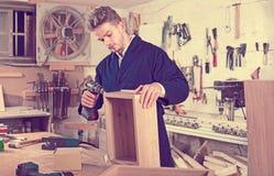 Mann, der Fach an der Werkstatt macht Lizenzfreies Stockbild