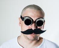 Mann, der falschen Schnurrbart und Schutzbrillen trägt Stockfotografie