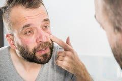 Mann, der Falten auf seinem Gesicht betrachtet stockfoto