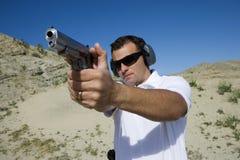 Mann, der Faustfeuerwaffe auf Schießstand in der Wüste abzielt Lizenzfreie Stockfotos