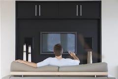 Mann, der Fernbedienung im Wohnzimmer verwendet Stockfotografie