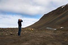 Mann, der Ferngläser in den Bergen bei Svalbard verwendet Stockbild