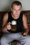 Mann, der fernsieht und Bier trinkt Stockbild