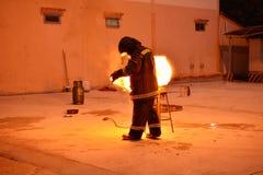 Mann in der Feuershow nach den ausbildenden Feuerwehrmännern, proben von den Feuerwehrmännern vom Kochen Stockfotos