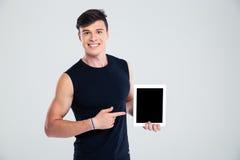 Mann, der Finger auf leerem Tablet-Computer-Schirm zeigt Stockfotografie