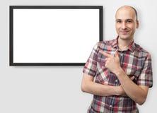 Mann, der Finger auf Plasmafernsehapparat zeigt Lizenzfreie Stockfotos