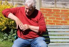 Mann, der Finger und Hand hält Schmerzliche Arthritis Lizenzfreie Stockbilder