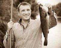Mann, der Fische nach der Fischerei hält Stockfotografie