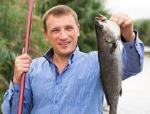 Mann, der Fische nach der Fischerei hält Stockfotos