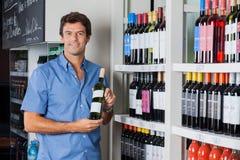 Mann, der Flasche Alkohol am Supermarkt hält Stockbild