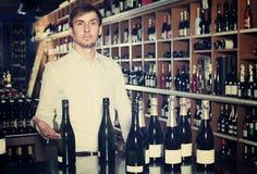 Mann, der Flasche Wein wählt Lizenzfreie Stockfotografie