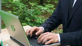 Mann in der formellen Kleidung schreibend auf dem Laptop, der im Wald, umweltfreundliche Technologie sitzt stock video
