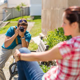 Mann, der Foto der Frau auf Bank macht Lizenzfreie Stockfotografie