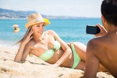 Mann, der Foto der Frau auf Strand macht Stockbilder