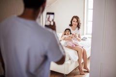 Mann, der Foto seiner schönen Frau und entzückenden Kindes macht lizenzfreie stockbilder