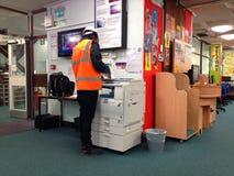 Mann, der Fotokopierer in einer öffentlichen Bibliothek verwendet Stockbilder