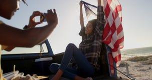 Mann, der Fotos der Frau mit Handy auf dem Strand 4k macht stock footage